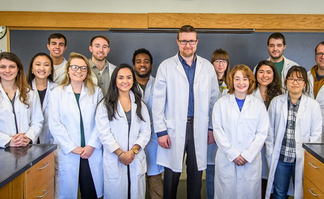 professor and students in lab coats in lab
