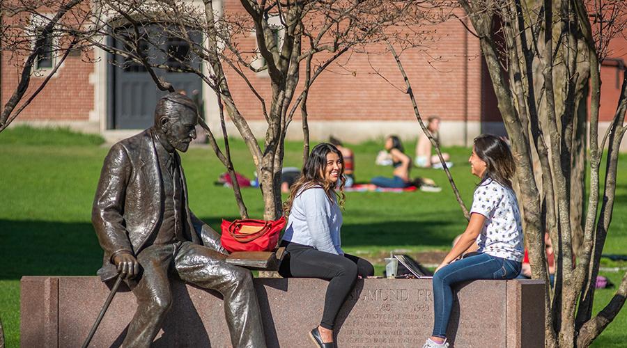 girls sitting on wall with sigmund freud statue