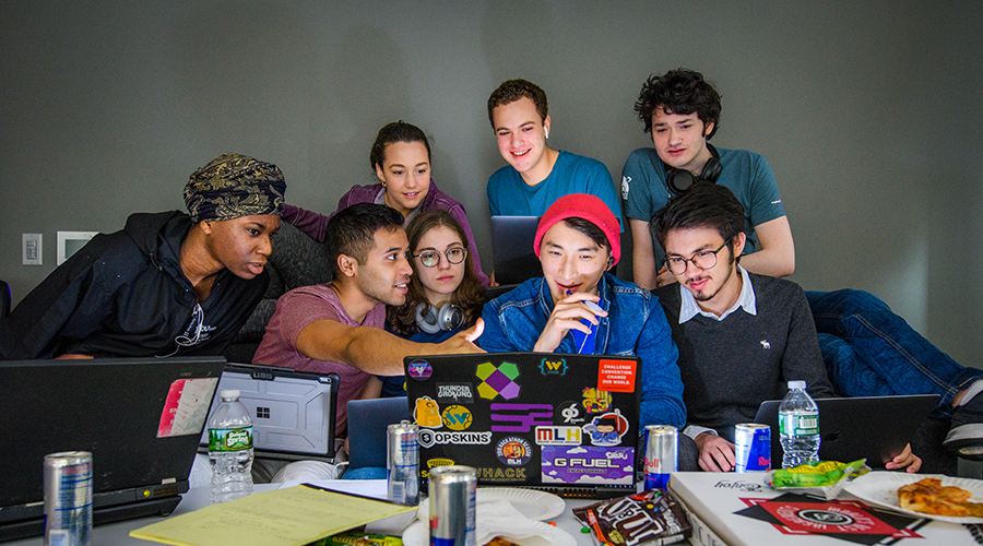 students all looking at pc with junk food all over desk