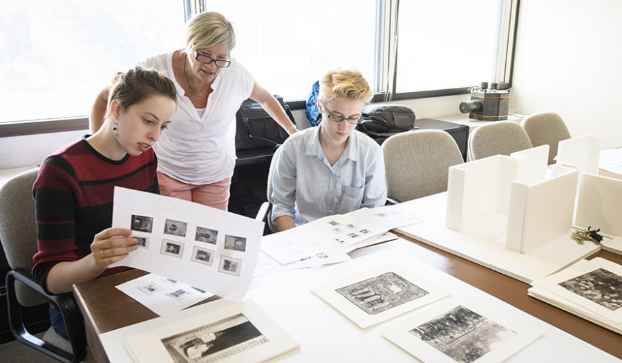woman standing behind two students looking over drawings