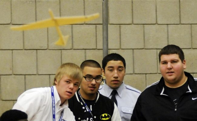 4 male young students flying paper plane