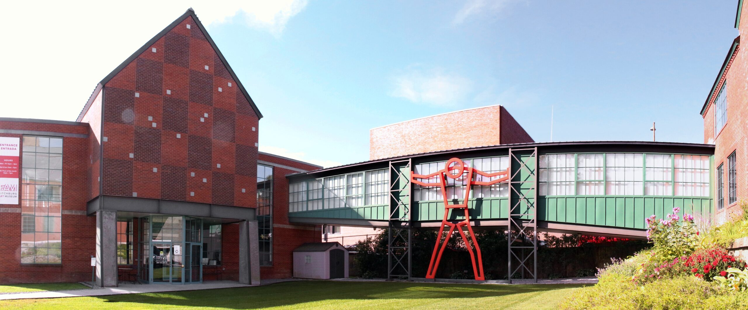 Front facade of the Fitchburg art museum - brick building with glass walkway and sculptural person supporting walls