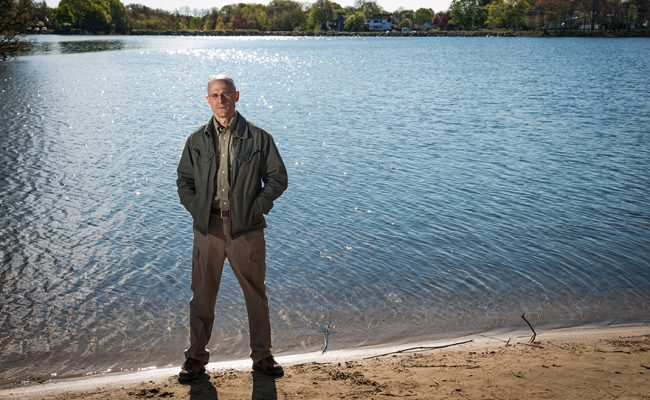 Researcher standing at edge of pond