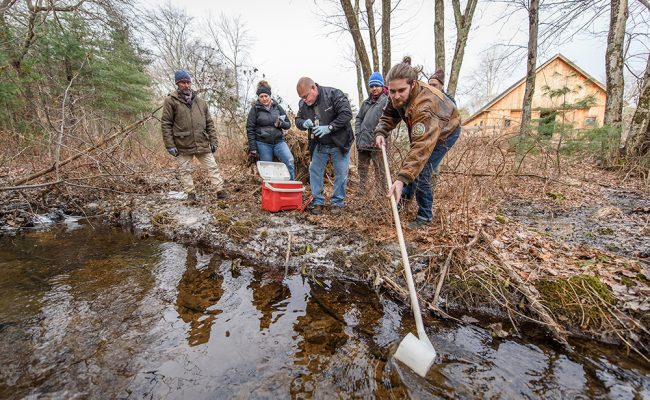 Four researchers gathering water samples from pond