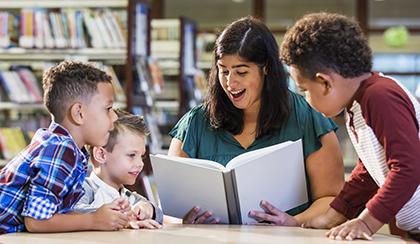 Teacher with three preschoolers reading book