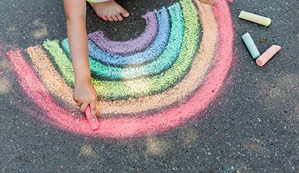 Child drawing rainbow on sidewalk