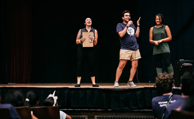 college students on stage putting on performance for young k-12 students