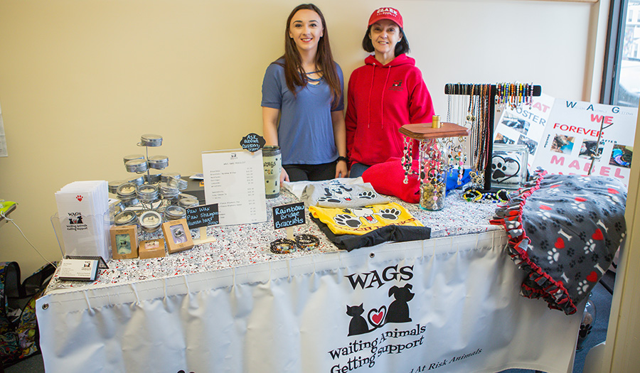 Student and volunteer selling products at table