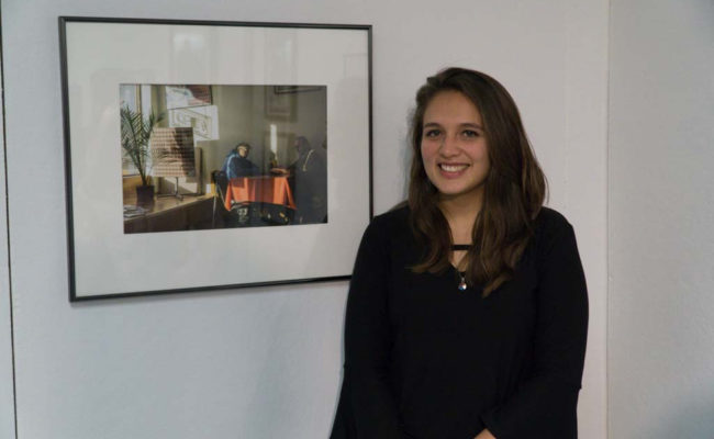 girl posing in front of her photography art at show
