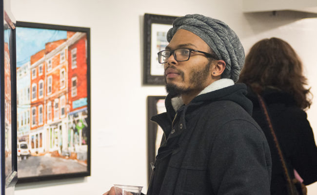 male student looking over art at show