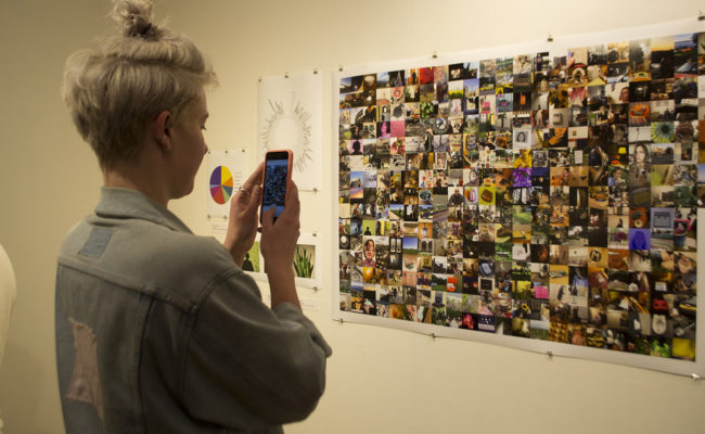 Girl taking picture of photo collage
