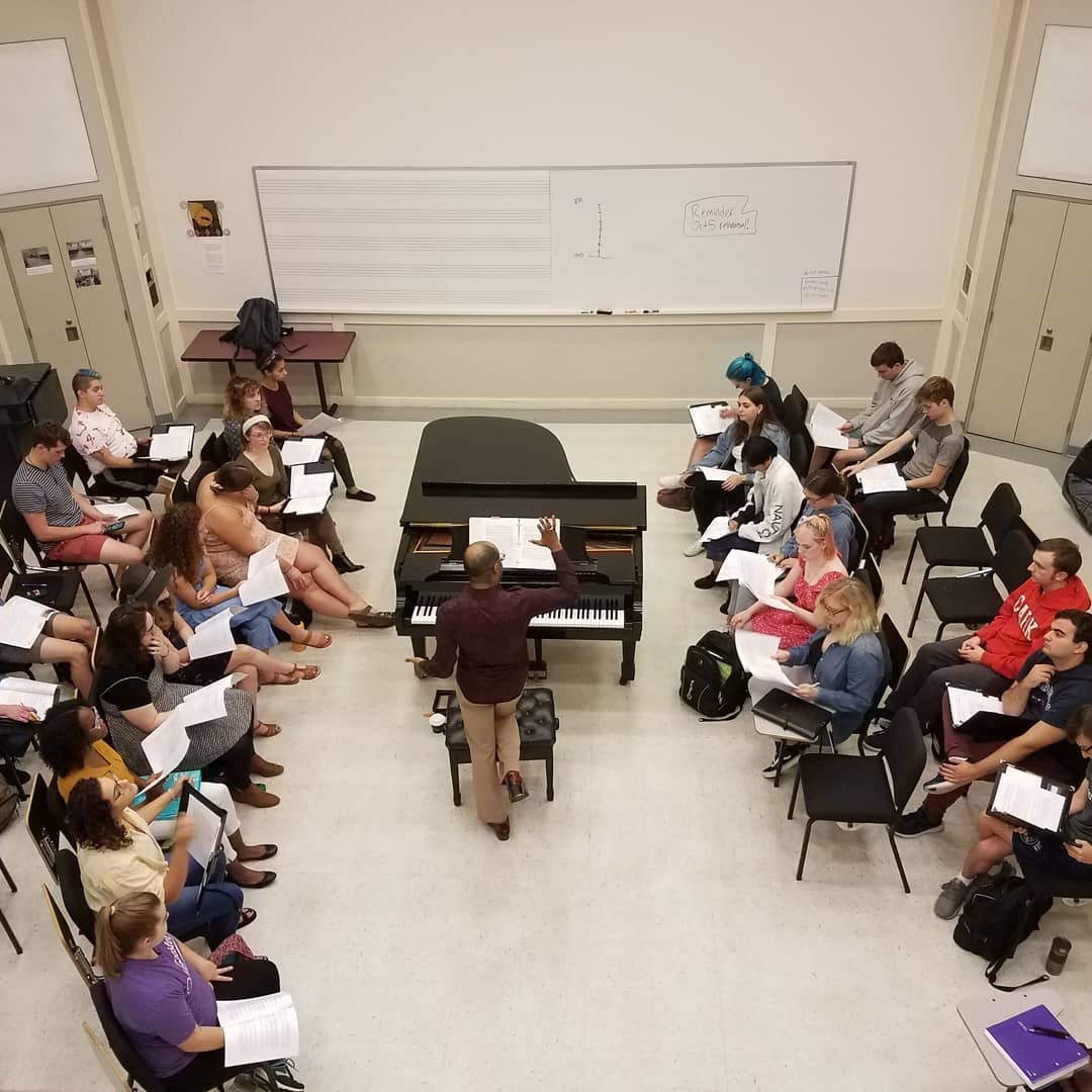 Professor Cailin Manson instructs students in front of a piano