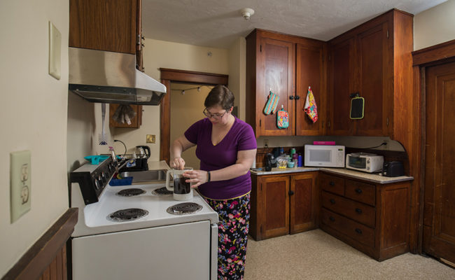 graduate housing: 926 Main St. Apartment Kitchen with female cooking at stove