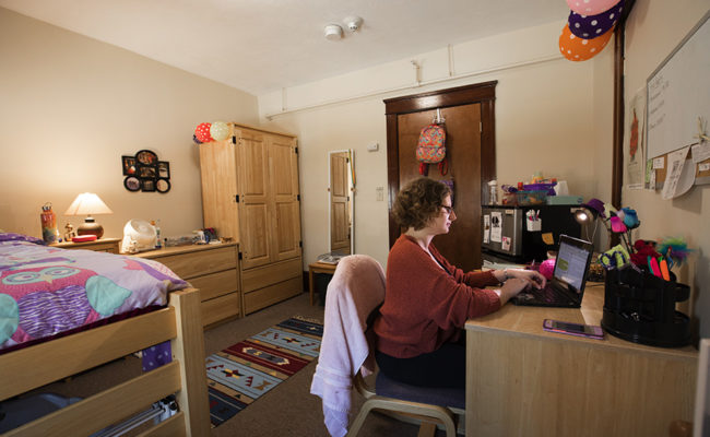 graduate housing: 926 Main St. Apartment Bedroom with female sitting at desk