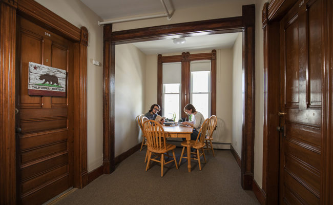 graduate housing: IDCE House 906 Main St. Living Area with two students sitting at table