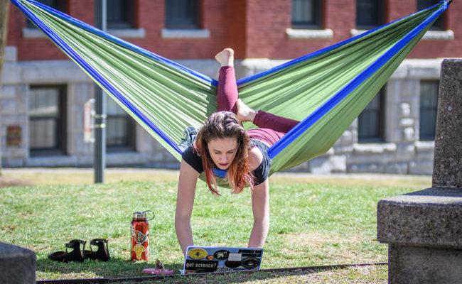 Clark student studying upside down on hammock
