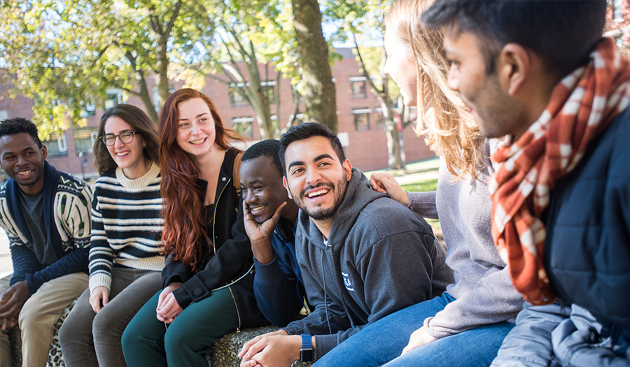 diverse students sitting on wall