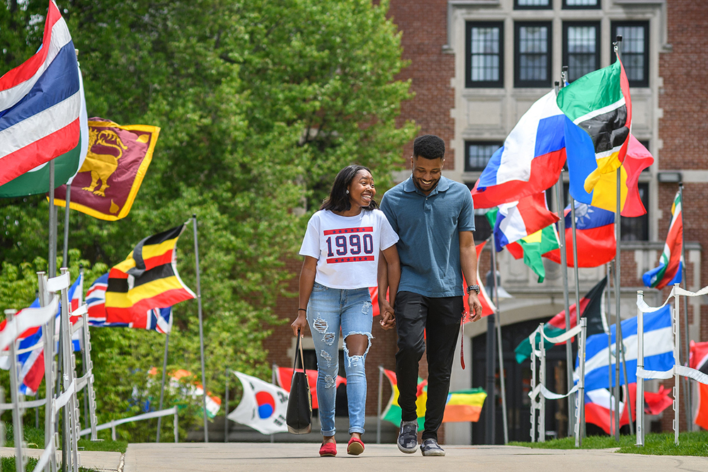 two students wlking down path with international flags