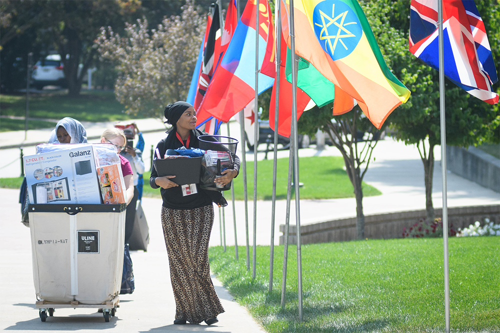 International student walking up ramp with housing items for move in day