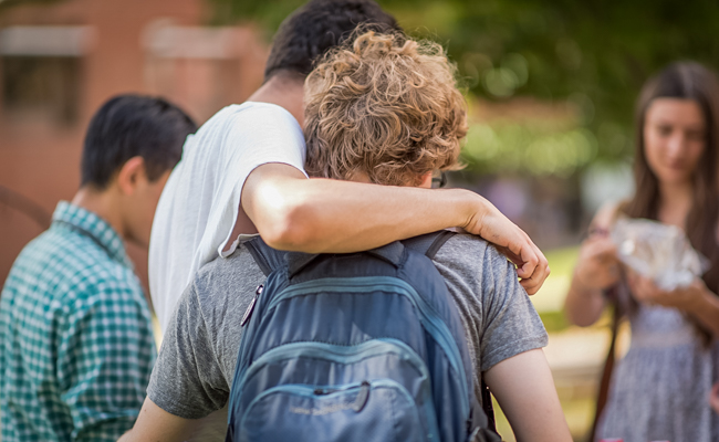 male student with arm round another male student