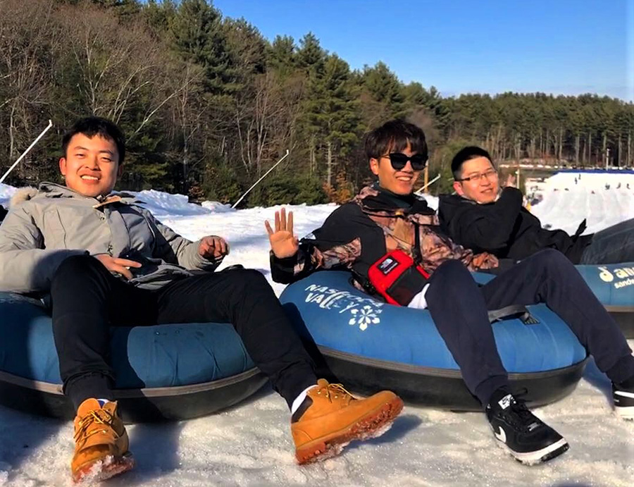 students sitting on snow tubs
